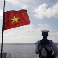 A member of the Vietnamese military stands guard on Thuyen Chai Island in the Spratly archipelago. Vietnam on Wednesday accused a Chinese vessel of intentionally ramming two of its ships in an area of the disputed South China Sea where Beijing has deployed a giant oil rig. | REUTERS