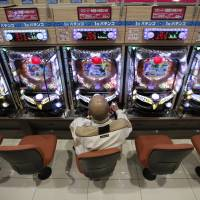 A visitor plays Pachinko at a Dynam Japan Holdings Co. pachinko parlor in Koga, Ibaraki Prefecture, last month. | REUTERS