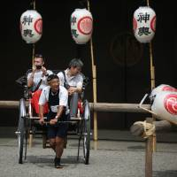 Tourists ride a rickshaw at Asakusa Shrine on the Sensoji Temple compound in Tokyo on May 14. | AP