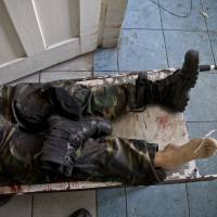 The body of a pro-Russian gunman killed in clashes with Ukrainian government forces near the airport in the city of Donetsk, Ukraine, lies on a stretcher at a morgue on Tuesday. | AP
