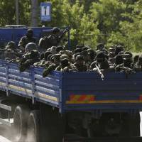 Pro-Russian militiamen arrive in a truck to take positions outside the airport in Donetsk, Ukraine, on Monday.   AP