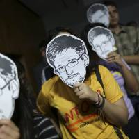 Protesters hold up masks of former U.S. National Security Agency contractor Edward Snowden during testimony before a Brazilian Congressional committee on the NSA's surveillance programs, in Brasilia in August 2013. The U.S. government is close to ending the NSA's nationwide bulk collection of American phone records through an overwhelming House vote on Capitol Hill. | REUTERS
