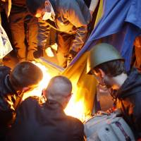 Pro-Russia protesters burn a Ukrainian flag outside the district council building in Donetsk, eastern Ukraine, on Sunday. | REUTERS