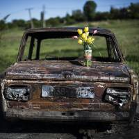 A bouquet of flowers is placed atop the burned-out shell of a car at the site of clashes between pro-Russia gunmen and the Ukrainian army, 4 km north of Slovyansk, on Wednesday. | AP