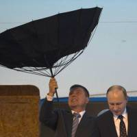 A member of Russian President Vladimir Putin's security detail struggles with an umbrella as Putin exits a plane upon arriving for a summit in Shanghai on Tuesday. | AFP-JIJI