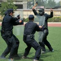 Policemen take part in counterterrorism training in Shijiazhuang, northern China, on Tuesday after six people were wounded in a knife attack at a Chinese train station. | AFP-JIJI