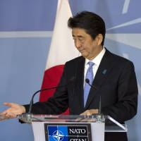 Prime Minister Shinzo Abe (left) and NATO Secretary-General Anders Fogh Rasmussen participate in a press conference at NATO headquarters in Brussels on Tuesday. | AP