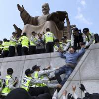 Policemen detain university students on a statue of King Sejong the Great during a protest in central Seoul on Thursday demanding President Park Geun-hye resign over the Sewol ferry disaster. | REUTERS