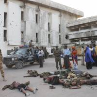People gather around the bodies of killed Somali soldiers after an attack on parliament in Mogadishu on Saturday. | AFP-JIJI