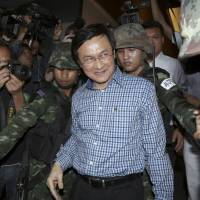 Former Thai Education Minister Chaturon Chaisang is seized by soldiers after emerging from hiding and giving a surprise news conference in Bangkok on Tuesday. In it, he assailed the military for its coup and for appointing senior officers to run ministries they know little about. | AP