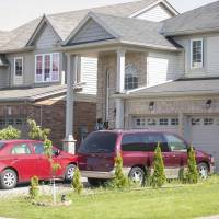 Vehicles are seen parked outside a home on Friday in London, Ontario, Canada, where, according to local media, a 10-year-old boy was found by police and Children's Aid workers after having allegedly been confined in a room for nearly two years by his aunt and uncle. | REUTERS