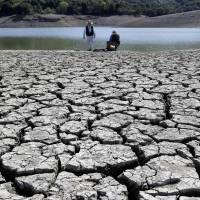 This March 13 photo shows cracks in the dry bed of the Stevens Creek Reservoir in Cupertino, California. The Obama administration is more certain than ever that global warming is changing Americans' daily lives and will worsen — conclusions that scientists will detail in a massive federal report to be released Tuesday. | AP