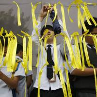 A student ties a yellow ribbon to a memorial for victims of the Sewol ferry disaster in Chuncheon on Thursday. | AFP-JIJI