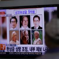 A man watches a TV news program about Yoo Byung-eun, the fugitive businessman whose family members ran the shipping company which operated the Sewol ferry, in Seoul on Monday. | AP