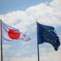 The Hinomaru flies beside the European Union flag as Prime Minister Shinzo Abe and German Chancellor Angela Merkel held a news conference at the Chancellery in Berlin last Wednesday. | BLOOMBERG