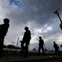 Thai soldiers carry out a patrol after a clean-up operation at a pro-government demonstration site on the outskirts of Bangkok on Friday. | AP