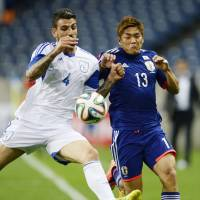 In pursuit: Cyprus' Giorgos Merkis (left) and Japan's Yoshito Okubo vie for the ball in second-half action on Tuesday. | KYODO