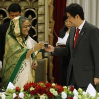 Bangladeshi Prime Minister Sheikh Hasina toasts Japanese counterpart Shinzo Abe during a banquet in Tokyo on Monday. | AFP-JIJI