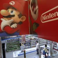 Shoppers browse under the Nintendo corporate logo and characters from the company's 'Super Mario' video game at an electronics store in Tokyo on Wednesday. | AP
