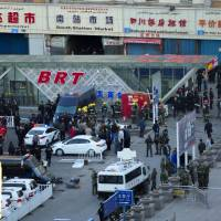Security personnel gather near the scene of an explosion outside the Urumqi South Railway Station in Urumqi in China's Xinjiang Uigur Autonomous Region on Wednesday after an explosion killed three and injured dozens as President Xi Jinping wrapped up a four-day visit there. | AP
