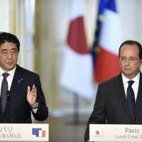 Prime Minister Shinzo Abe (left) speaks alongside French President Francois Hollande at a joint press conference Monday at the Elysee presidential palace in Paris. | AFP-JIJI