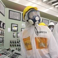 Wearing a protective suit, U.S. Ambassador to Japan Caroline Kennedy inspects the central control room for the Unit 1 and Unit 2 of Tokyo Electric Power Co.'s wrecked Fukushima No. 1 nuclear power plant Wednesday. Kennedy toured the crippled plant for about three hours. | POOL