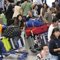 Vacationers crowd the international arrival lobby of Narita airport Monday, the day before the end of Golden Week. | KYODO