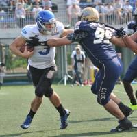 Pressure on the quarterback: Obic defensive tackle Yoshihiro Nakada rushes IBM quarterback Kevin Craft, forcing him to scramble during the second quarter. Craft was held to one touchdown pass in the game.   HIROSHI IKEZAWA