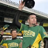 Center of attention: Tigers hurler Randy Messenger (right) tips his cap to the fans after Hanshin's 1-0 win over the Yomiuri Giants on Sunday at Koshien Stadium. | KYODO