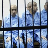 Former Prime Minister Baghdadi Mahmudi (left) and former Minister of Foreign Affairs Abdul Ati al-Obeidi in deposed leader Moammar Gadhafi's government sit behind bars during a hearing at a courtroom in Tripoli on April 27. | REUTERS