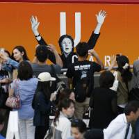 Fans take photos of a poster of singer Paul McCartney after his concert at National Stadium in Tokyo was canceled Sunday. | REUTERS