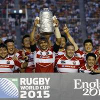 See you in England: Japan captain Michael Leitch lifts the trophy as the Brave Blossoms celebrate their win over Hong Kong on Sunday. Japan claimed the Asian Five Nations title and a spot in the 2015 Rugby World Cup with the win. | AP