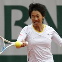 Early exit: Kimiko Date-Krumm returns the ball to Russia's Anastasia Pavlyuchenkova during their first-round match at the French Open on Tuesday in Paris. Date-Krumm lost 6-3, 0-6, 6-2. | AP