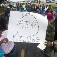 K.K. Davis (left) and Tommy Jones of Hearne carry a sign with other protesters outside the Hearne, Texas, police department on Thursday after Tuesday's shooting of 93-year-old woman. | BRYAN COLLEGE STATION EAGLE/AP