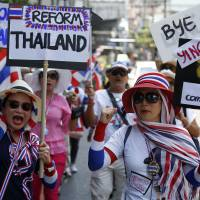 Anti-government protesters carry signs against ousted Prime Minister Yingluck Shinawatra in central Bangkok on Thursday. | REUTERS