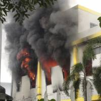 Smoke rises from a fire at a Maxim company building in Binh Duong province on Wednesday. Thousands of Vietnamese set fire to foreign factories and rampaged in industrial zones in the south of the country in an angry reaction to Chinese oil drilling in a part of the South China Sea claimed by Vietnam, officials said Wednesday. | REUTERS