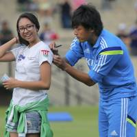 Japan soccer player Yasuhito Endo signs an autograph  for a fan prior to a training session at Sorocaba Municipal Stadium on Sunday. | REUTERS