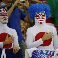 Japan's fans sing the national anthem Saturday before the start of their 2014 World Cup Group C soccer match against Cote d'Ivoire at the Pernambuco arena in Recife, Brazil. | REUTERS