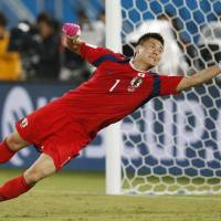 Japan goalkeeper Eiji Kawashima jumps to save the ball during Thursday's match against Greece.