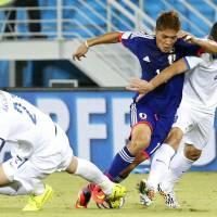 Japan striker Yoshito Okubo vies with Greece defenders during Thursday's Group C match against Greece.