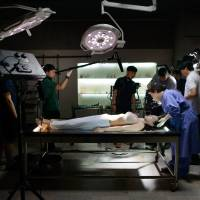 A television crew prepares for a take during filming for the South Korean medical drama 'Quiz From God' at a studio near Paju on June 3. | AFP-JIJI