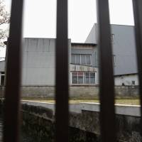 A former Kameda Co. factory used as a dormitory for its Chinese workers is photographed through railings in Hakusan, Ishikawa Prefecture, on April 16. | REUTERS