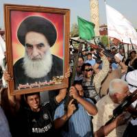 Armed Iraqi Shiite tribal fighters gathered in Baghdad's Sadr City on Wednesday hold up a large portrait of the country's top Shiite cleric, Grand Ayatollah Ali al-Sistani, during a rally against the Islamic State of Iraq and the Levant. | AP