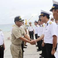 A Philippine Navy officer greets his Vietnamese counterparts upon arrival Sunday on Southwest Cay in the disputed Spratly Islands.   REUTERS