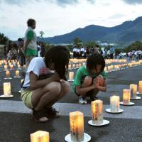 Mourners pray on Tuesday for those killed when Mount Unzen erupted in 1991 above Shimabara, Nagasaki Prefecture. | KYODO