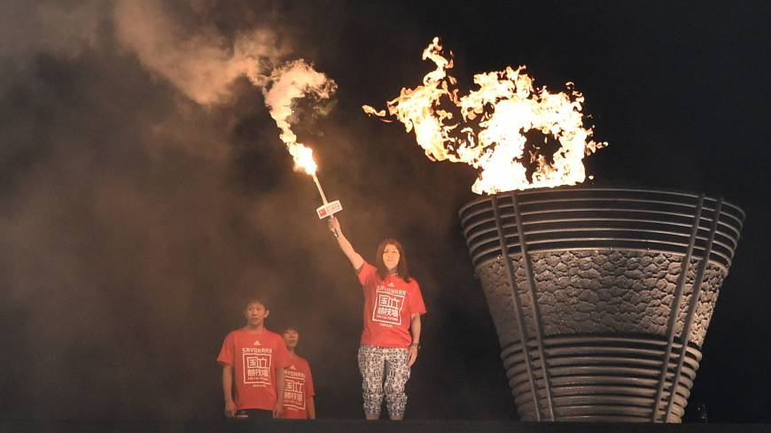 Olympic wrestling gold medalist Saori Yoshida lights a torch during the farewell ceremony Saturday for Tokyo's National Stadium.