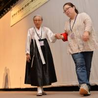 South Korean Kim Bok-dong, 88, is helped off stage after speaking at the 12th Asian Solidarity Conference, a gathering of international activists, to demand that Japan formally atone for the sexual slavery it carried out in its wartime military brothels, on Saturday in Tokyo. Kim got pulled into the brothel system in 1941 at the age of 15. | AFP-JIJI