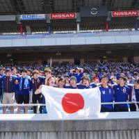 Soccer fans cheer at Nissan Stadium in Yokohama shortly the first-round match between Japan and Cote d'Ivoire kicked off Sunday at the 2014 World Cup. | KAZUAKI NAGATA