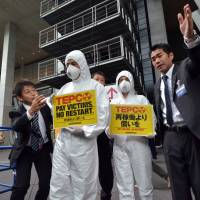 Wearing radiation suits and masks, anti-nuclear activists from Greenpeace are asked to stay away from Tokyo Electric Power Co.'s annual shareholders' meeting in Chiyoda Ward, Tokyo, on Thursday. | AFP-JIJI