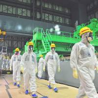Officials from the International Atomic Energy Agency inspect the Fukushima No. 1 nuclear power plant on Nov. 27, as part of a review of efforts to decommission the wrecked complex. | AFP-JIJI
